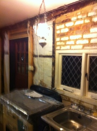 South wall of kitchen and side door, stripped back to brick