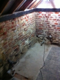 East and south walls of bathroom, brick and timbers exposed