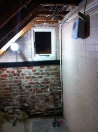 South and west walls of bathroom, brick and timbers exposed