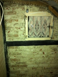 North wall of bathroom showing window and bricks exposed