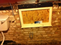 East wall of bathroom and window with timbers stripped