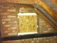 Window in north wall of bathroom with new mortar between surrounding bricks