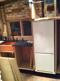 Kitchen sink and refrigerator with partially-completed cabinets